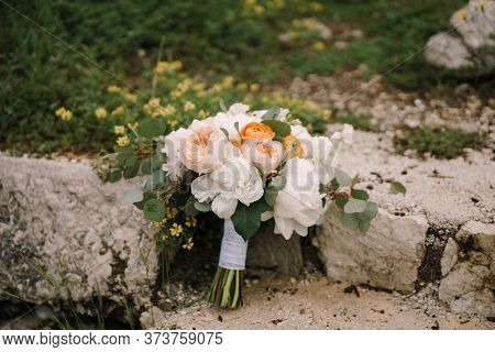 Bridal Bouquet Of White Peonies, Cream Roses, Orange Buttercups And Branches Of Eucalypt Tree On A S
