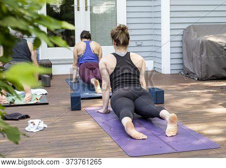 Women Doing A Virtual Yoga Class At Home Outside During Covid-19 Coronavirus Pandemic.  Social Dista