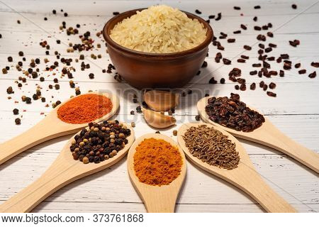 Ingredients For Cooking Pilaf: Rice In A Ceramic Bowl In The Background, Garlic In The Foreground, B
