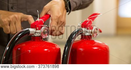 Fire Fighter Pull The Safty Pin Of Fire Extinguishers Tank In The Building Concepts Of Fire Preventi