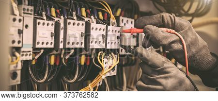 Electrical Engineer Using Digital Multi-meter Measuring Equipment To Checking Electric Current Volta