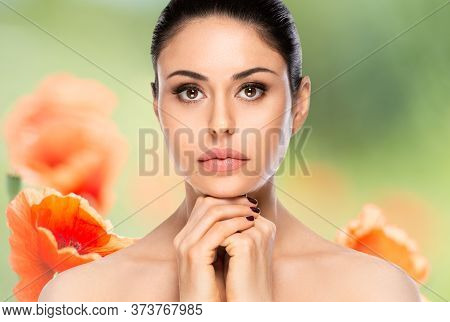 Beautiful Woman Face Portrait Over Flowered Blurred Background. Beauty Skin Care Concept.