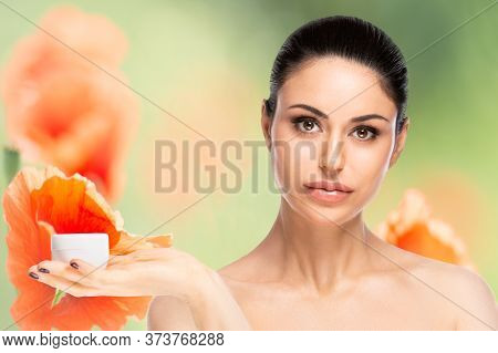 Skincare Concept.young Pretty Woman Holding Cosmetic Cream Jar Over Flowered Blurred Background