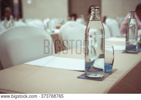 Water Bottles On Table In Meeting Room Or Conference Hall With Group Audience Listens Speech Lecture