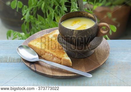 Cream Of Corn Soup And Cheese Toast Bread  On Wooden Plate