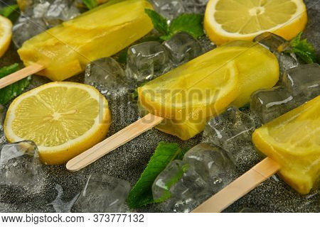 Close Up Frozen Fruit Juice Popsicles With Fresh Lemon Slices, Green Mint Leaves And Ice Cubes On Gr