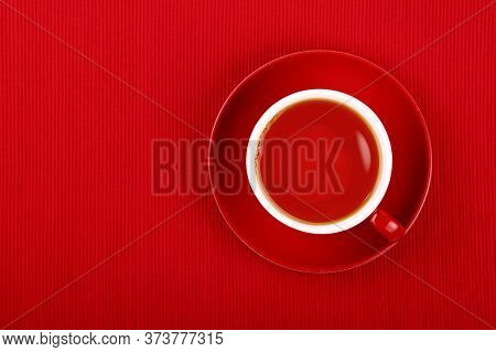 Close Up One Cup Full Of Black Or Fruit Tea On Saucer Over Red Tablecloth, Elevated Top View, Direct