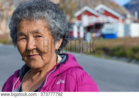 Sisimiut, Greenland - August 17, 2019: Portrait Of A Local Inuit Senior Woman Looking Camera In Sisi