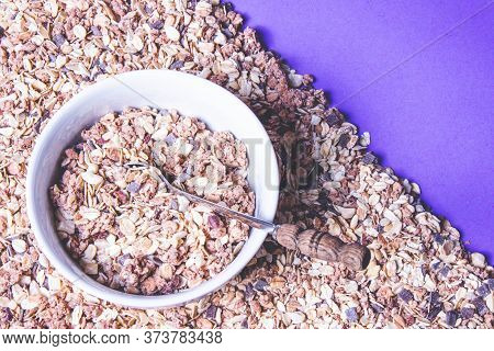 Half Are Scattered With Your Favorite Muesli On A Purple Background And In A Plate Full With Muesli