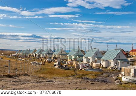 Pond Inlet, Baffin Island, Canada - August 23, 2019: Residential Wooden Houses On A Dirt Road Next T