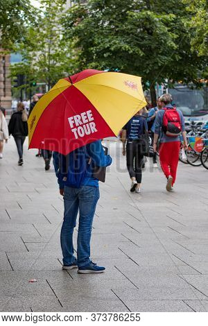 Belfast, Northern Ireland, Uk - July 30, 2019: A Man Standing At The City Hall Holding An Umbrella P