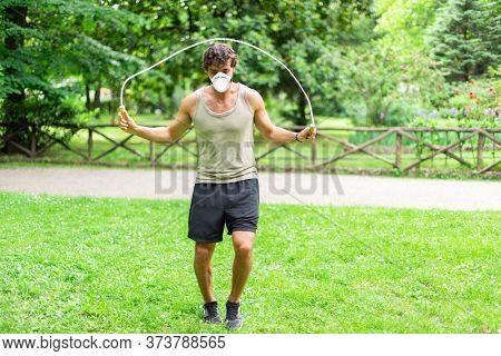 Masked man jumping a rope outdoors, cardio and stamina workout during coronavirus pandemic
