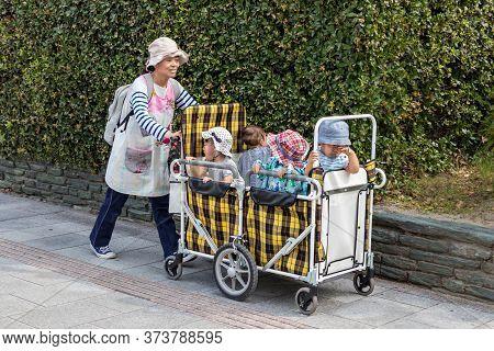 Hiroshima, Japan - September 30, 2019: A Japanese Babysitter - Kindergarter Teacher Carrying Four Ki