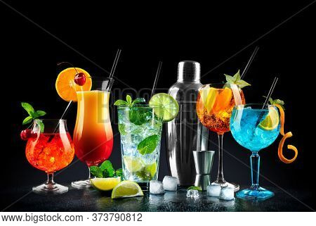 Set of various cocktails with shaker on black background