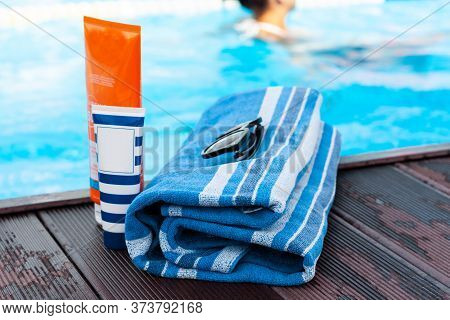 Sun Glasses, Tube Of Sunscreen Cream, Blue Towel Near Swimming Pool, Tropical Background.