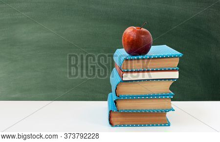 Back To School, Pile Of Books And Red Apple With Empty Green School Board Background. Distance Home