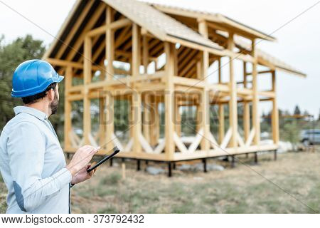 Architect Or Builder With Digital Touchpad Near The Wooden House Structure, Building And Designing W