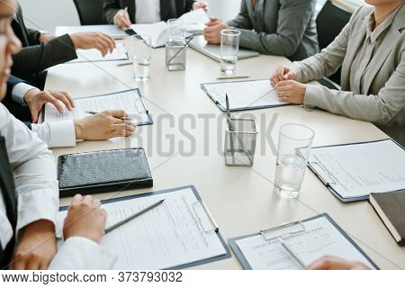 Large group of business partners or colleagues or conference participants learning financial papers or contract at meeting in boardroom