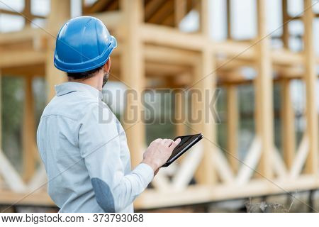 Architect Or Builder Supervising A Project With A Digital Touchpad Near The Wooden House Structure,