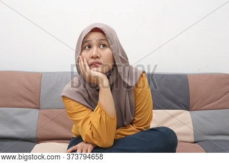 Beautiful Asian Muslim Woman Thinking Something Seriously While Sitting On Sofa, Girl With Contempla