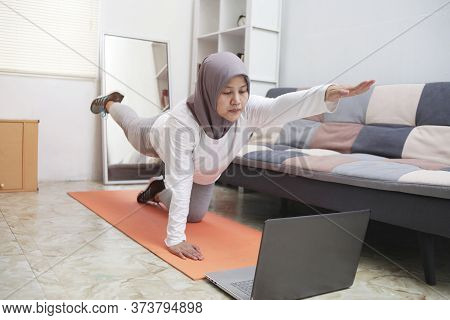 Asian Muslim Woman Wearing Hijab Doing Exercise At Home While Watching Online Video Instruction On L