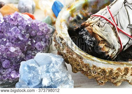 A Close Up Image Of An Amethyst Geode And White Sage Smudge Bundle.