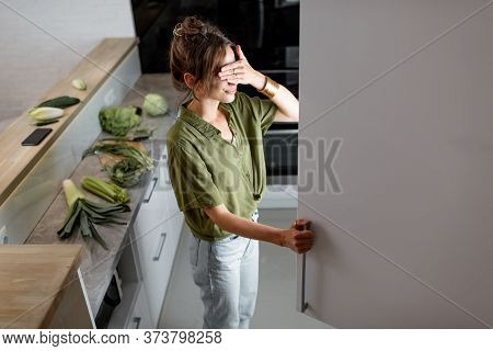 Young Woman Looking Into The Fridge, Feeling Hungry At Night. Concept Of Not Regular Eating And Over