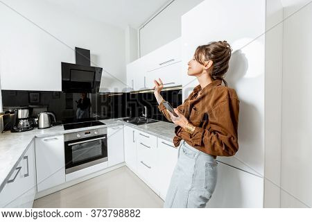 Young Woman Controlling Kitchen Appliances With Mobile Phone And Voice Commands, Wide Interior View.