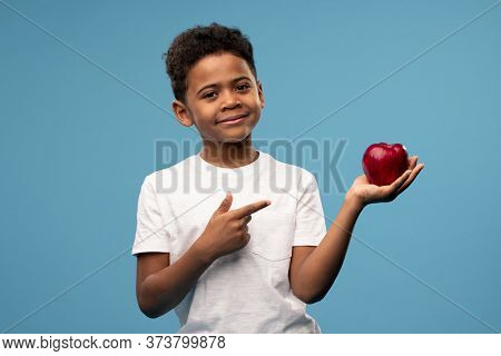 Happy little African boy with big red ripe apple in hand pointing at the fruit and looking at you while recommending it as healthy food