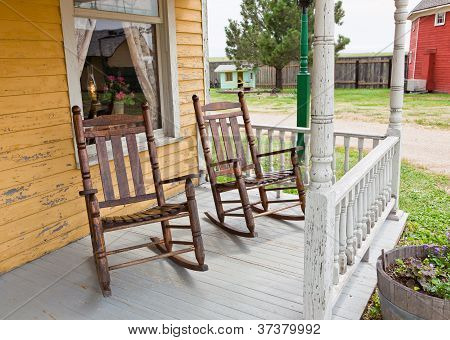 Two hardwood rocking chairs on the white washed porch of an old western house with yellow pealing paint and lace curtain framed window. poster