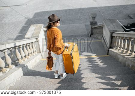 Young Female Traveler Walking Down The Stairs With A Suitcase, Traveling In The Old City