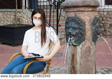 Сaucasian Young Woman In Protective Mask On Her Face, Sitting In Wicker Chair Near Fountain. Works W