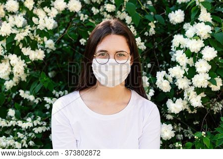 Portrait Young Woman In Protective Mask On Her Face. In Background Flowering Plant. Concept: Solo In