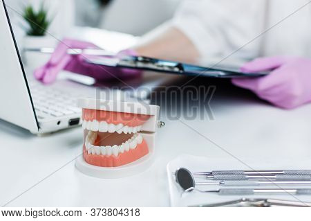 Dentist Holding Medical Exam Card Of Patient And Using Computer In Dentist's Clinic. Teeth Care And