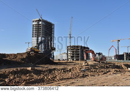 Excavators On Earthworks. Backhoe On Road Work Digs Ground. Work Of Tower Cranes At Construction Sit