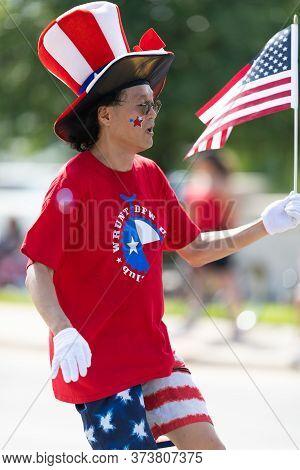 Arlington, Texas, Usa - July 4, 2019: Arlington 4th Of July Parade, Man Riding An Unicycle Waving Th