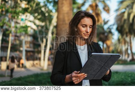 Woman Using Wireless Earphones Selects Music Holding Laptop Computer While Relaxing Park In Barcelon