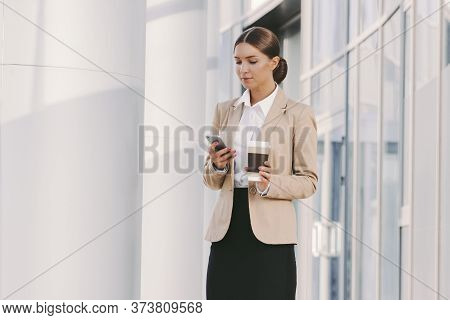 Portrait Young Beautiful Business Woman In Stylish Suit Use Smart Phone And Drink Coffee Outdoors. A