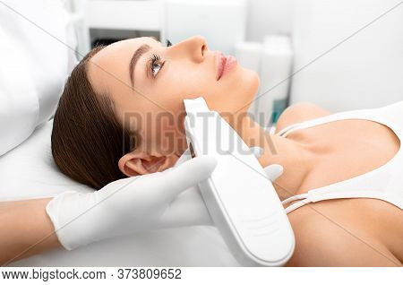 Woman Getting Ultrasonic Peel Skin, A Cleansing Procedure Using A Special Device. Procedure Ultrason