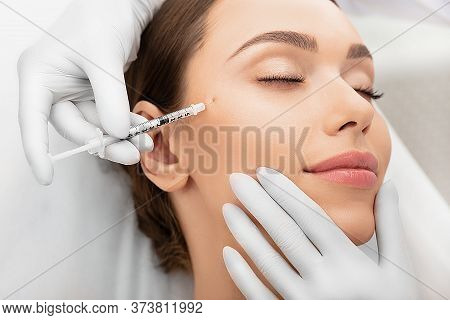 Beautiful Woman During Facial Mesotherapy. Beautician Doing Anti-aging Injection For Tighten Skin.