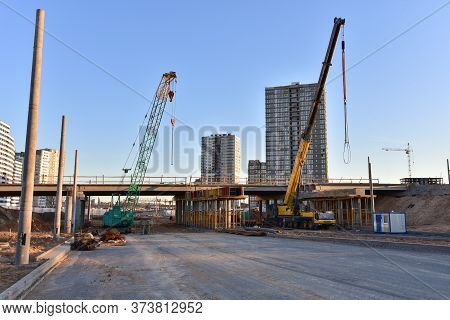 Work Of Truck Crane And Crawler Crane On Bridge Project Works. Roundabout Traffic Bridge Constructio