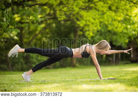 Attractive Girl Practicing Yoga. Young Woman Upward Plank Pose With Leg Up Outdoors In The Park, Cop