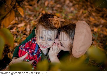 Happy Young Mother Playing And Having Fun With Her Little Baby Son On Sunshine Warm Autumn Day In Th