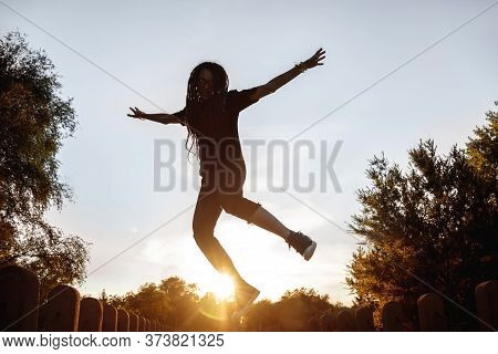 Silhouette Of A Jumping Girl On A Skateboard In The Setting Sun In The Park
