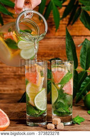 Iced Summer Drink With Citrus Fruits And Mint Pouring From Transparent Jug Into Glass On Wooden Back