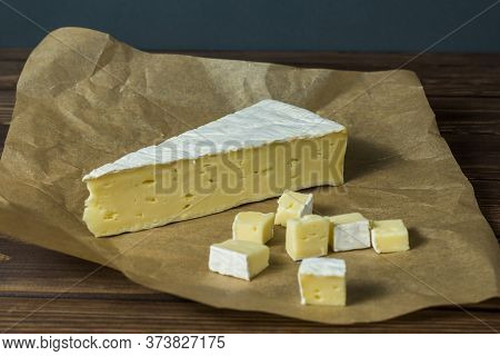 Brie Cheese. Tasting Cheese. Diced Cheese On Wrapping Paper On An Old Black Wooden Table. Food For W
