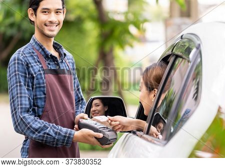 Portrait of asian restaurant employer hold credit card reader for asian woman customer to make mobile payment contactless technology on drive thru food service restaurant while picking up.