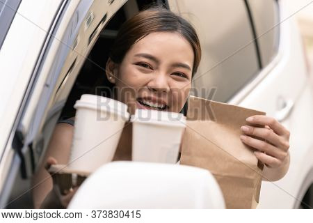 Asian Young adult in car holding disposable bag and coffee tray for take out food from drive thru service restaurant. Drive thru is new normal and popular service after coronavirus covid-19 pandemic.