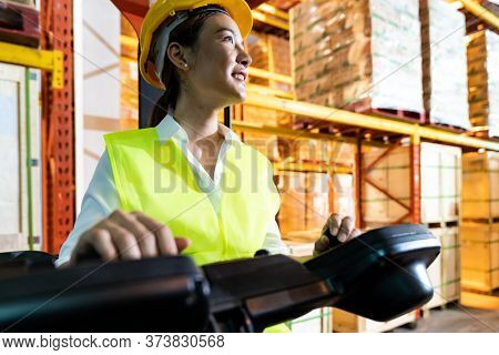 Portrait asian female warehouse worker using forklift truckin large warehouse distribution center. Business warehouse storage transportation and logistic concept