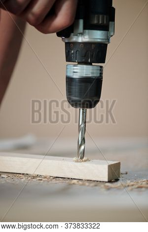 Close-up of unrecognizable furniture maker drilling wooden plank in joinery workshop